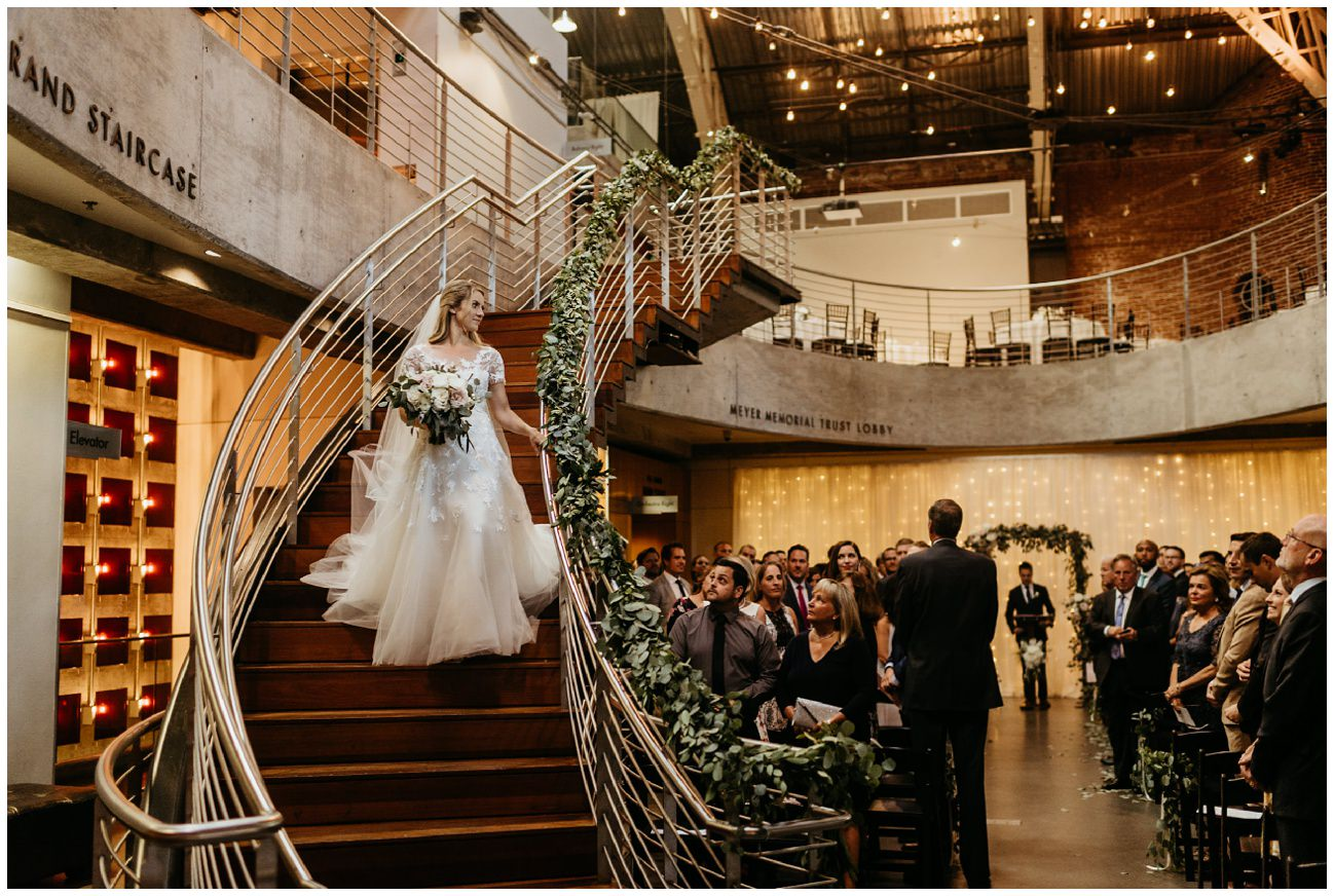 Darcy walks down the stairs at the armory wedding in portland Oregon